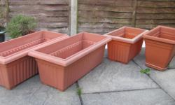 Four plastic planters. One has a tray and drainage