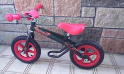 Red and black balance bike suitable for a child up to