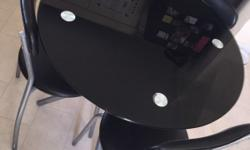 Black glass table available with 3 chairs. Only