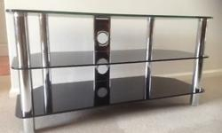 TV stand in black glass and chrome. 2 shelves. Will