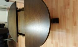 Dark solid oak extendable dining table, four chairs and