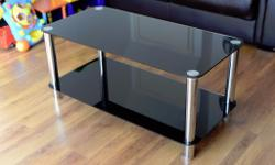 For sale is a glass topped coffee table unmarked with