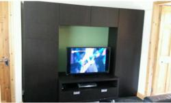 Black ikea wall units with shelving and tv stand with