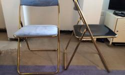 2x Gold metallic folding chairs. One is covered in blue