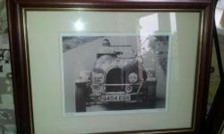 Picture of man and a dog in old fashioned car. Called